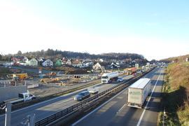 Autos und Lastwagen fahren auf der A8 im Enztal bei Pforzheim, daneben ist die Baustelle zu sehen.