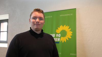 Felix Herkens vor einem Wahlplakat der Grünen mit Sonnenblumen.