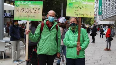 """Ein Mann und eine Frau in grünen Jacken und mit Atemschutz halten zwei Schilder hoch: """"Klimaschutz jetzt und für alle"""" sowie """"Nachhaltigkeit statt Profitgier"""" steht darauf, sowie jeweils """"Greenpeace Pforzheim""""."""