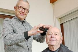 Ein Mann schneidet einem anderen die Haare.