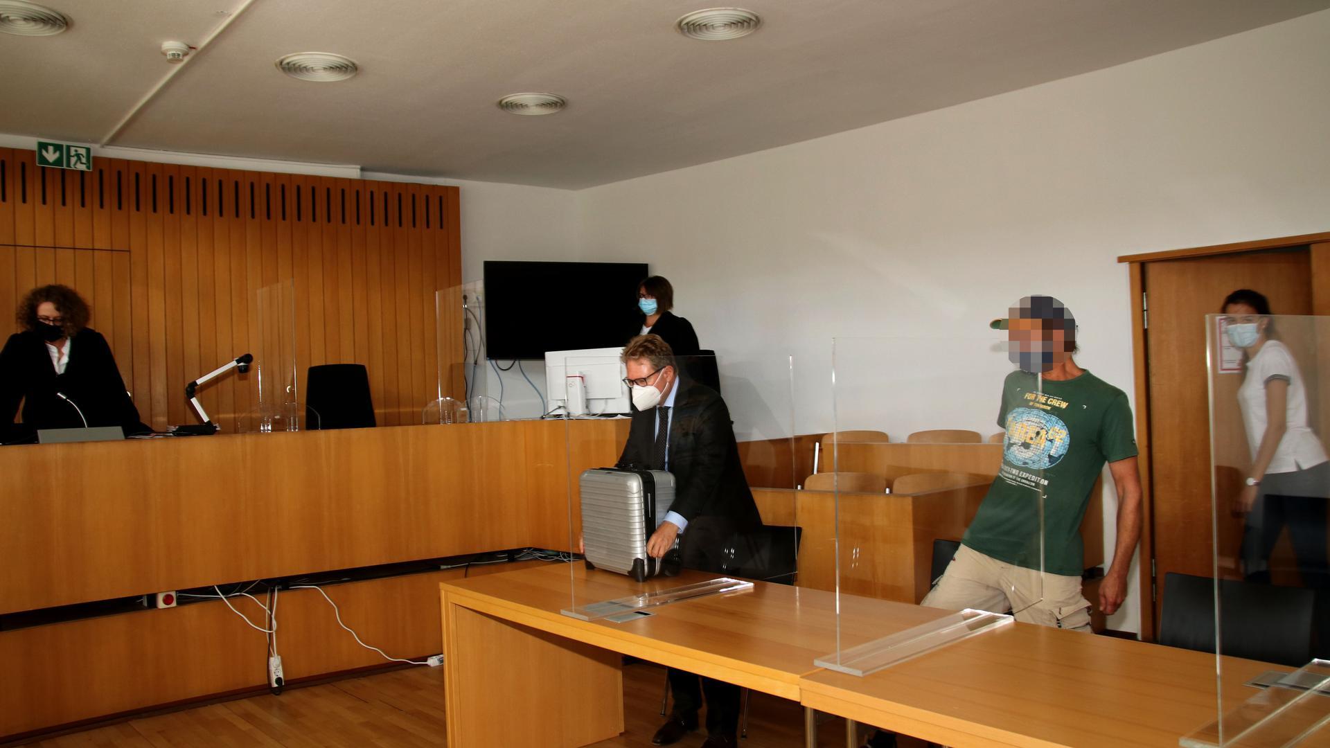 Amtsgericht Pforzheim, Sitzungssaal, Richterin, Verteidiger und stark verpixelter Angeklagter setzen sich hin.