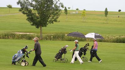 Drei Personen laufen mit Golfausrüstung über einen grünen Golfplatz.