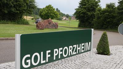 """Im Vordergrund steht ein Schild mit der Aufschrift """"Golf Pforzheim"""", dahinter ist grüner Rasen."""