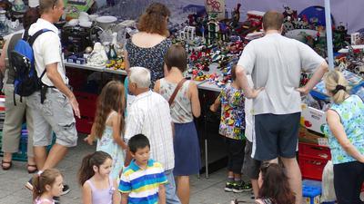 Mehrere Menschen stehen vor einem Flohmarktstand. Auf dem langen Tisch sind verschiedene Artikel wie Lego und Geschirr aufgebaut.