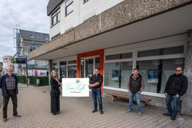 """Fünf Personen stehen vor einem Gebäude, eine Frau und ein Mann halten ein Plakat hoch, auf dem steht """"Unser Ländle Hohenwart."""""""