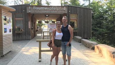 Eine Frau und ein Mann stehen Arm in Arm vor dem Eingang zum Baumwipfelpfad. Dieser ist eine Art hölzerner Durchgang, links und rechts sind Kassen.