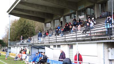 Zu sehen ist die Hauptribüne des Holzhofstadions beim letzten Spiel des CfR dort. Ein paar Menschen sitzen dort, darüber thront die gläserne Sprecherkabine.