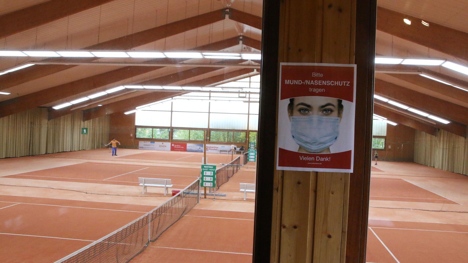 Die nahezu leere Tennishalle der PSG Pforzheim, drei Felder mit rotem Granulat. Im Hintergrund trainiert jemand, vorne ist ein Schild angebracht mit einem Hinweis, Maske zu tragen.