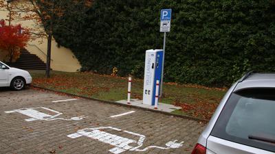 Eine Ladestation für E-Autos, davor zwei leere Parkplätze. Links und rechts stehen zwei Autos einrahmend.