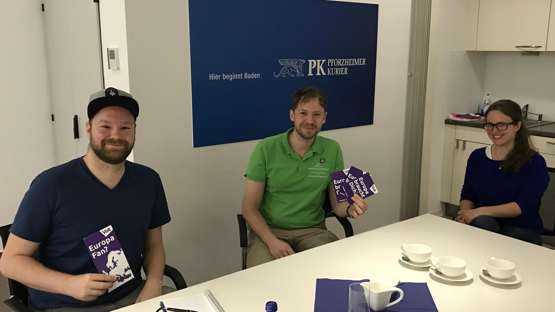 Drei Jungpolitiker sitzen in der Redaktion des Pforzheimer Kuriers und halten violette Broschüren von Volt in Händen.