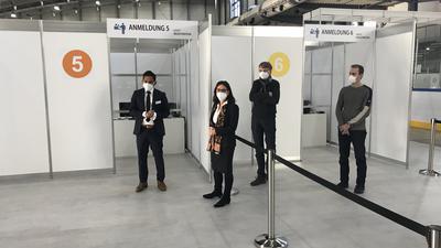 """Vier Menschen stehen vor Trennwänden und Schildern mit dem Titel """"Anmeldung"""""""