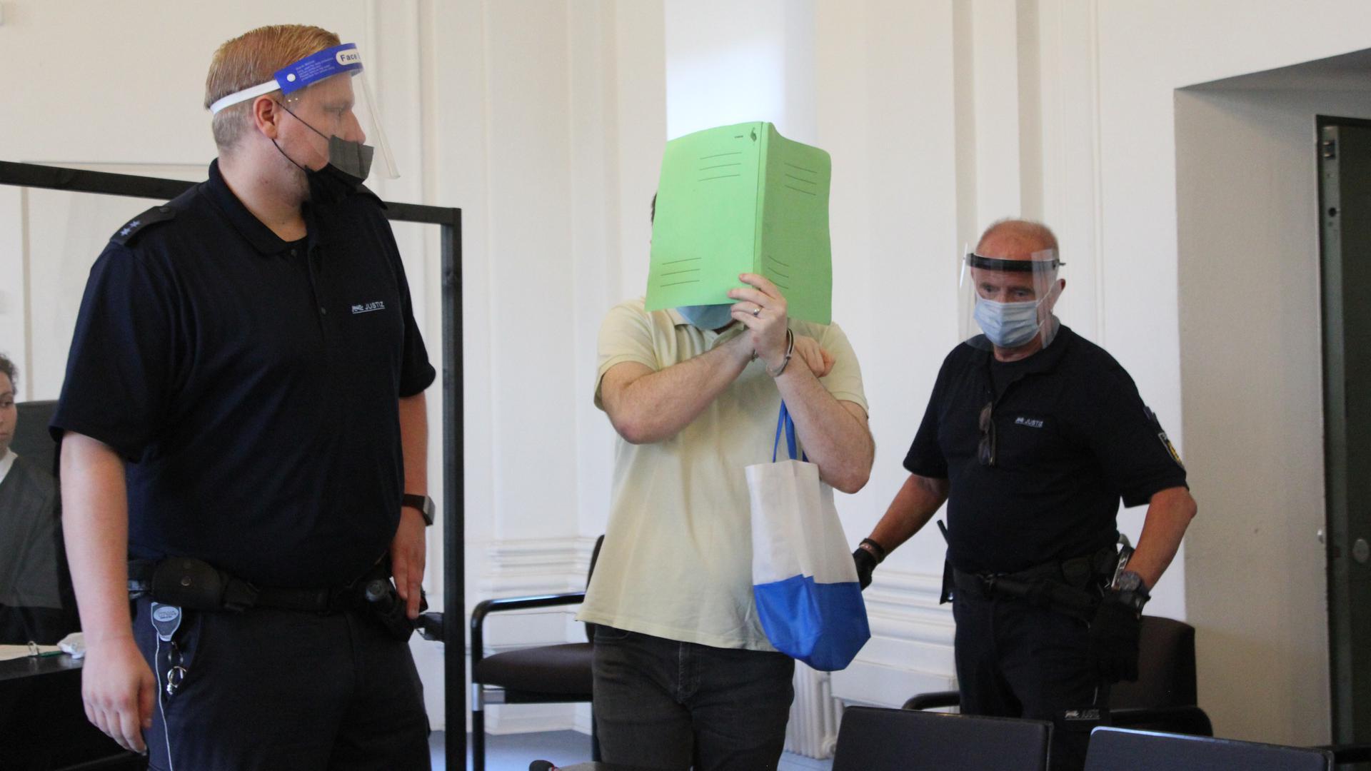 Zwei Sicherheitsleute führen den Angeklagten in den Schwurgerichtssaal.