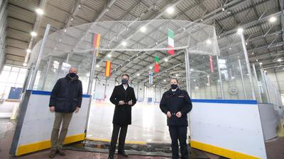 Drei Männer sehen nebeneinander vor einer Eisfläche, alle drei haben eine schwarze Maske auf.