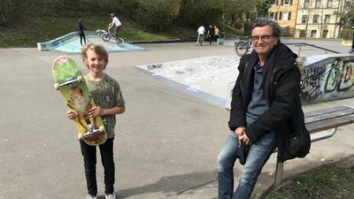 Ein Junge steht vor einem Skateplatz und hält sein Skateboard in den Händen. Neben ihm sitzt ein Mann auf einer Bank. Im Hintergrund sind andere Personen mit kleinen Fahrrädern und anderen Geräten.