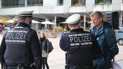 Zwei Polizisten weisen bei der Demonstration der Gegner der Corona-Auflagen vor dem Pforzheimer Rathaus auf die Maskenpflicht hin. Die meisten Teilnehmer trugen keinen Mundnasenschutz.