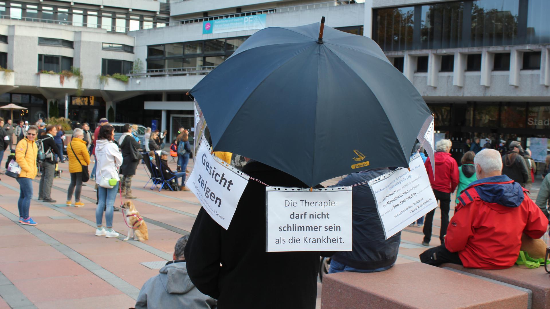 Teilnehmer bei der Corona-Demo auf dem Pforzheimer Marktplatz hält einen Schirm mit Zetteln und Botschaften.