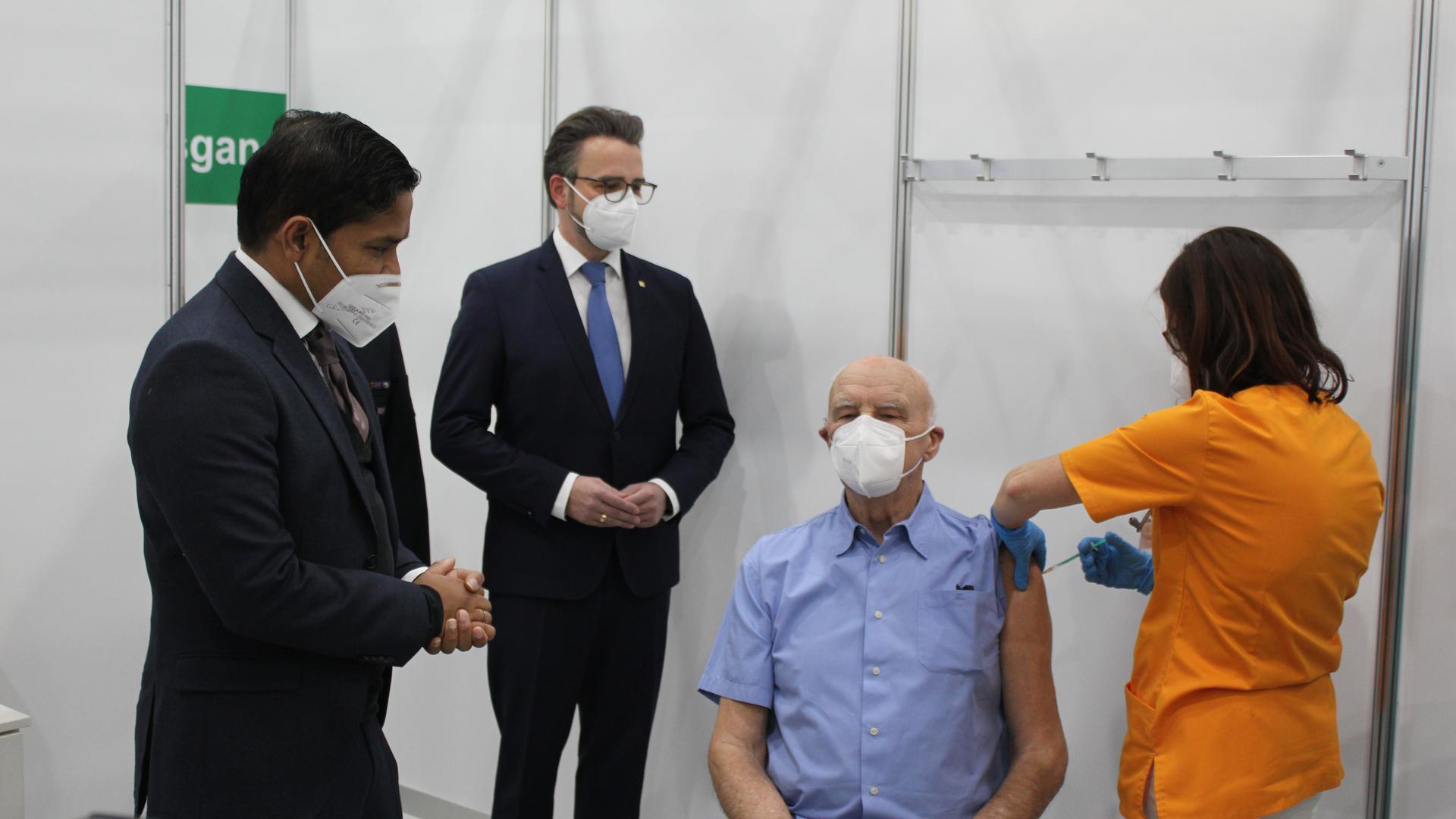 Ein Mann lässt sich von einer Frau impfen. Links neben ihm stehen zwei weitere Männer.