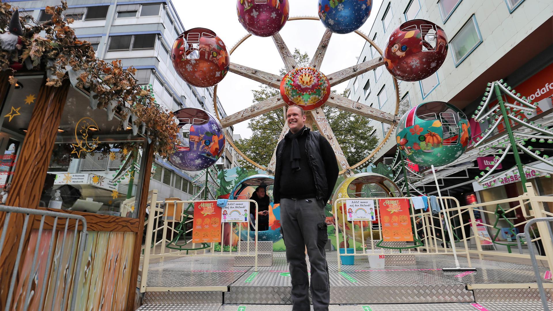 Schausteller Stefan Doss aus Waiblingen steht vor einem bunten Kinder-Riesenrad auf dem Pforzheimer Marktplatz