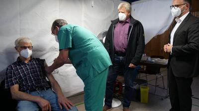 Vier Männer stehen in einem Zelt, einer wird geimpft.