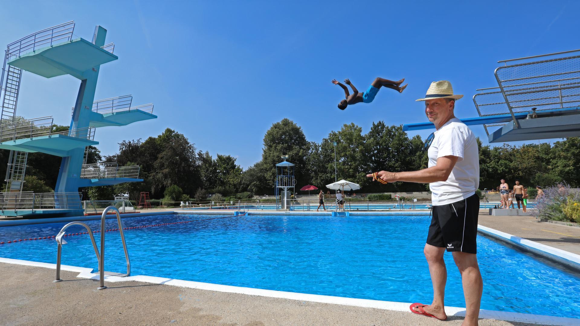 Jörg Augenstein mit Badeshorts, Flipflops und Strohhut  läuft an einem Schwimmbecken vorbei. Im Hintergrund springt ein Schwimmer vom Sprungturm.