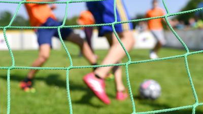 Kinder spielen auf einem Sportplatz Fußball.