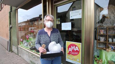 Eine Frau mit Maske steht vor einem Ladengeschäft.