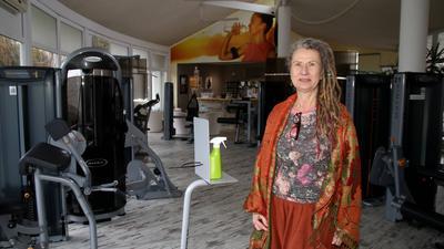 Frau mit Rasta-Locken und buntem Gewand steht inmitten von Fitnessgeräten in einer leeren Trainingshalle.