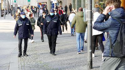 Zwei UNiformierte durchqueren zur Masken-Kontrolle die Innenstadt.