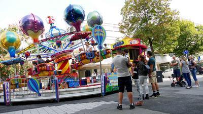 Mehrere Personen stehen vor einem Fahrgeschäft, das ein Karussell mit Heißluftballons ist.