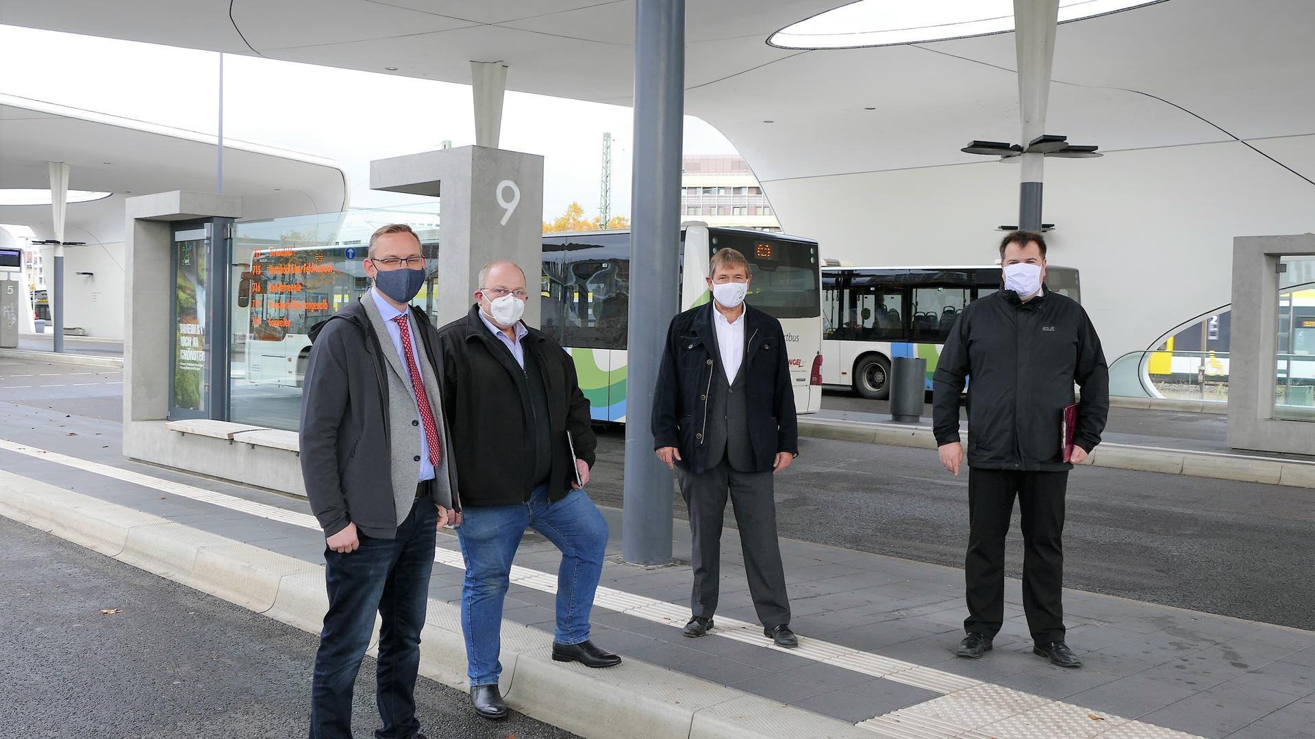 Vier Männer mit Masken stehen am Busbahnhof.