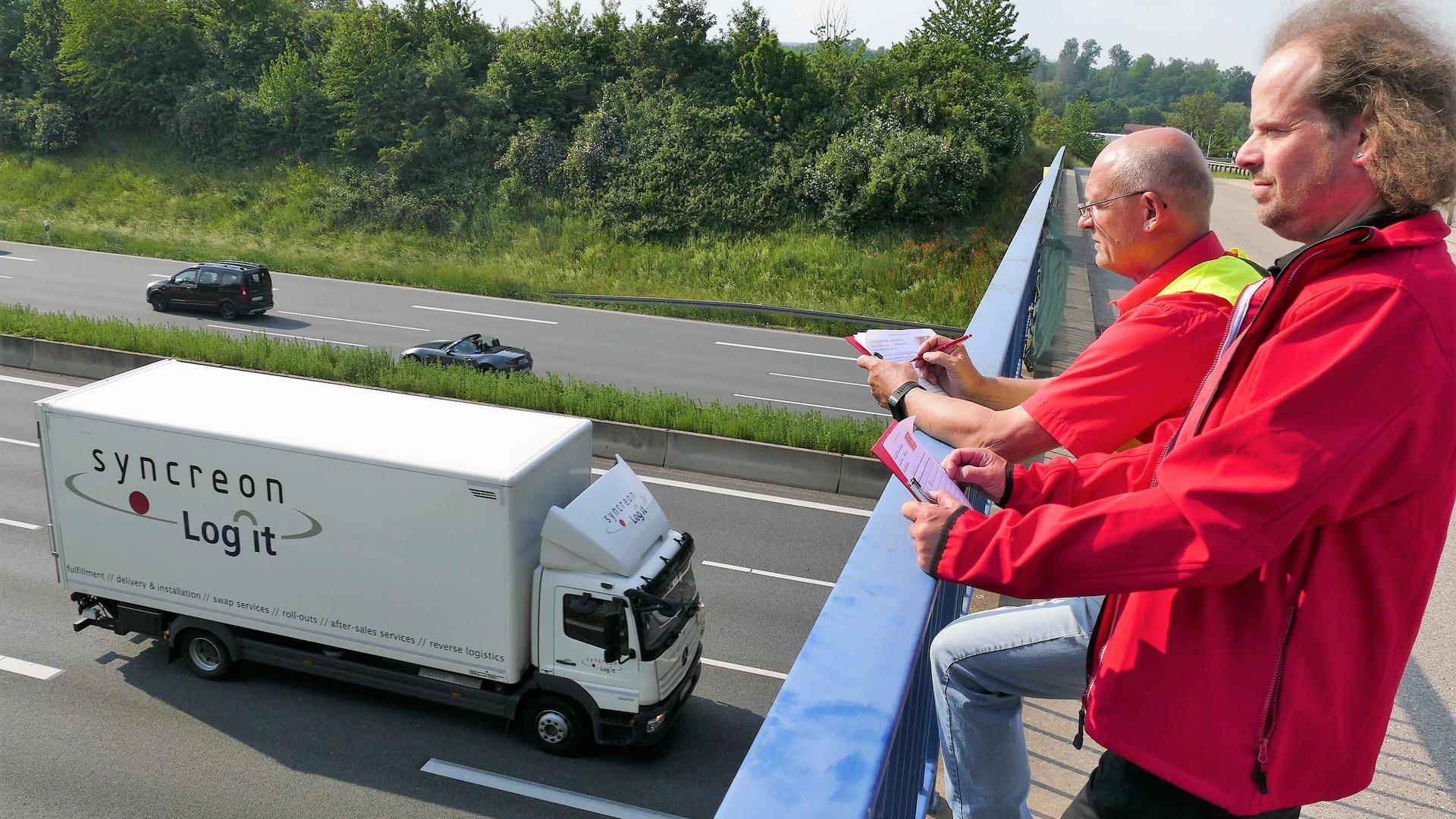 Zwei Männer auf Autobahnbrücke
