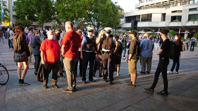 """Kundgebung zur Lage der Flüchtlinge in Lesbos vor dem Rathaus Pforzheim mit Polizei und zwei Mitglieder von """"Ein Herz für Deutschland"""" in roten T-Shirts, die in Richtung Platz von Kundgebungsteilnehmern abgeschirmt werden. Ralf Fuhrmann blaues Hemd von links"""