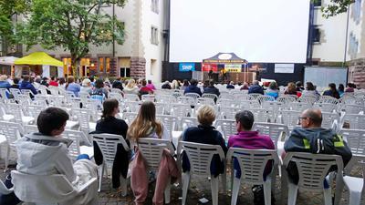 Stühle sind mit Blick auf die Leinwand aufgestellt, viele davon sind frei.