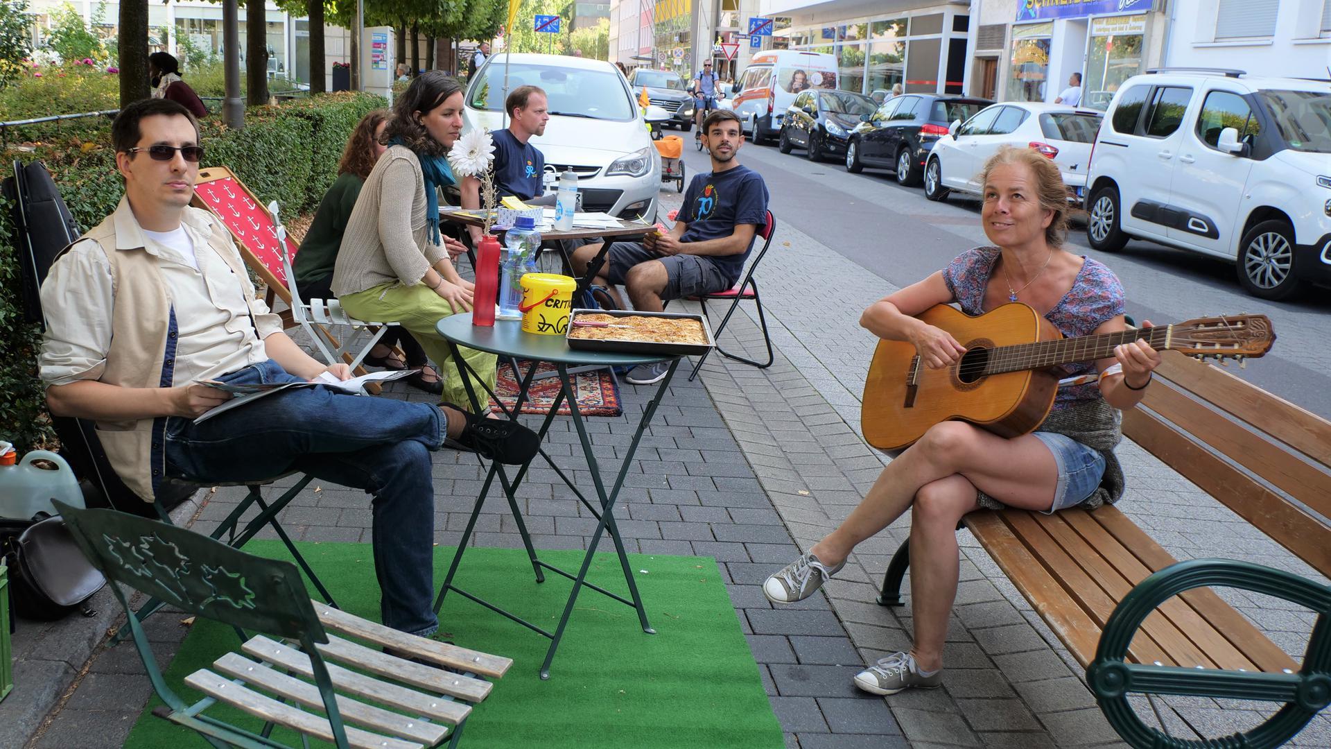 Mehere Personen sitzen gemütlich an Tischen in einer Parkzone an der Straße, eine Frau hat eine Gitarre in der Hand.