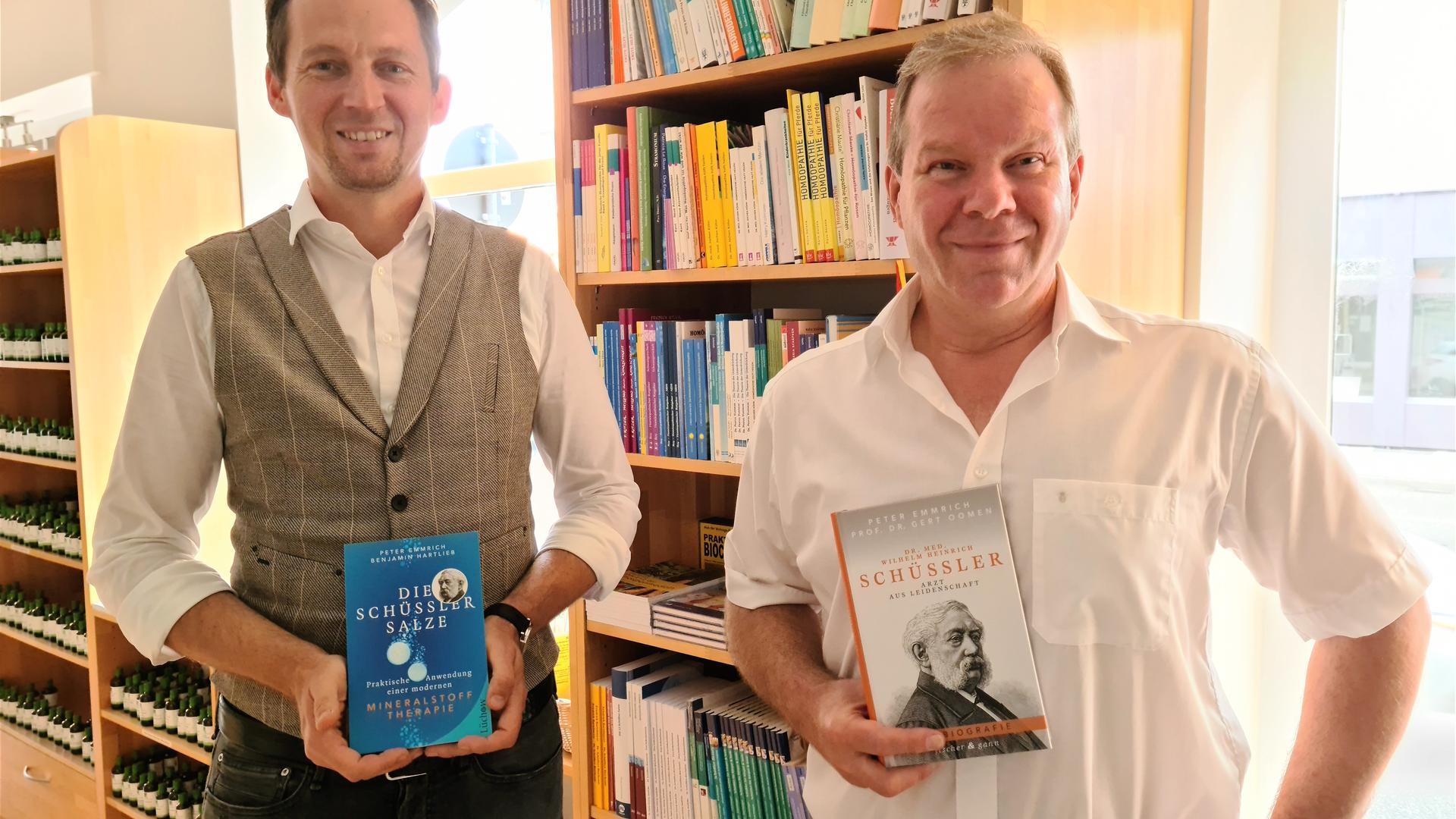 Zwei Männer stehen vor einem Buchregal und halten jeweils ein Buch in den Händen