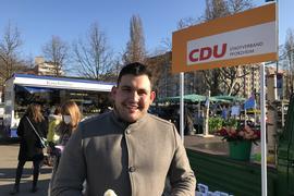 Ein Mann steht vor einem Wahlstand, im Hintergrund sind Marktstände.