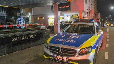 Ein Polizeifahrzeug steht neben einem Absperrband in Pforzheim.