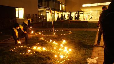 """Einen Kreis und """"9 %"""" haben die Streikenden mit LED-Lichtern und Sternregen in die Wiese vor dem Eingang zum Helios-Klinikum geschrieben."""