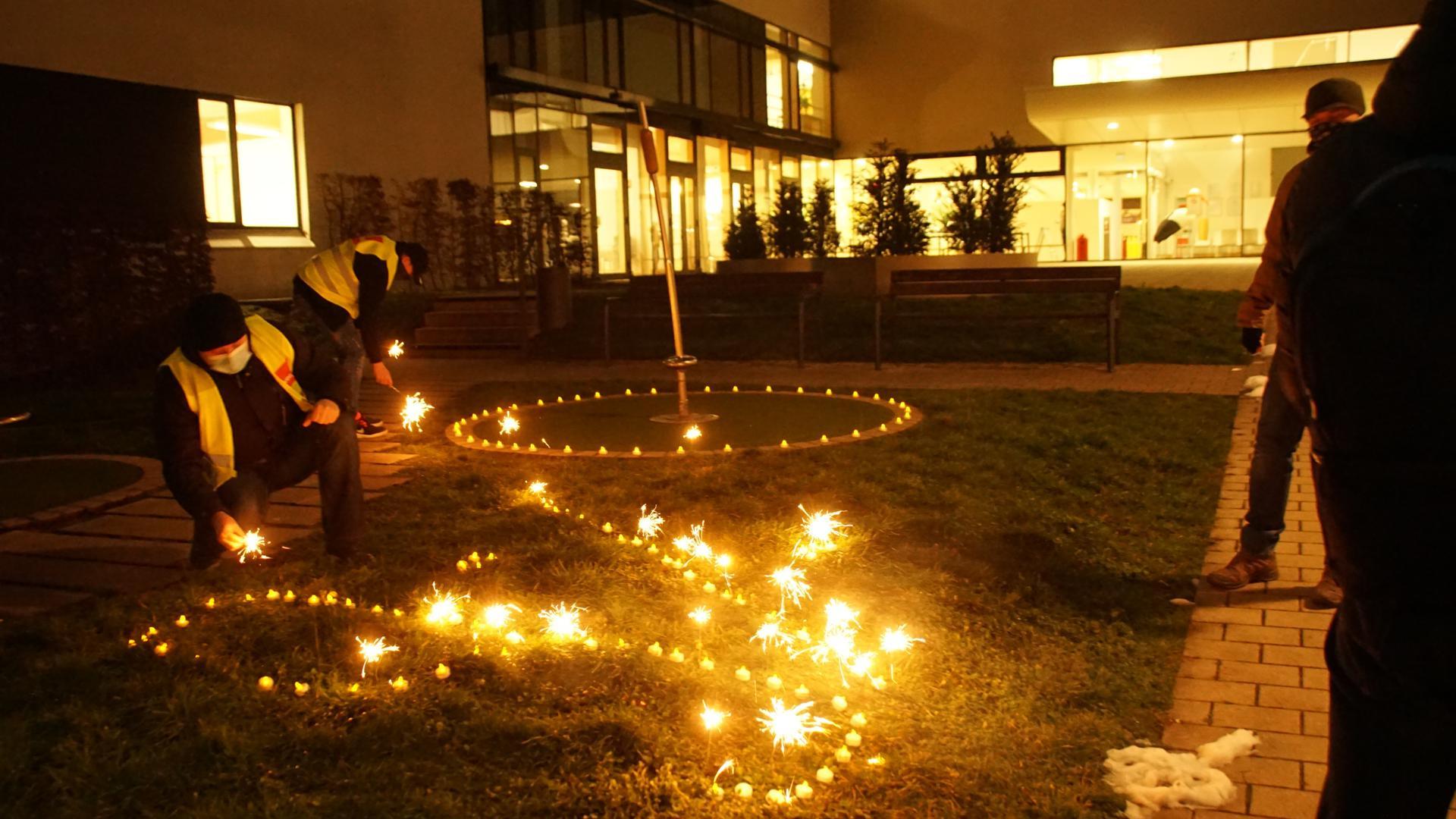 Sternregen und LED-Kerzen stecken in einer Wiese.