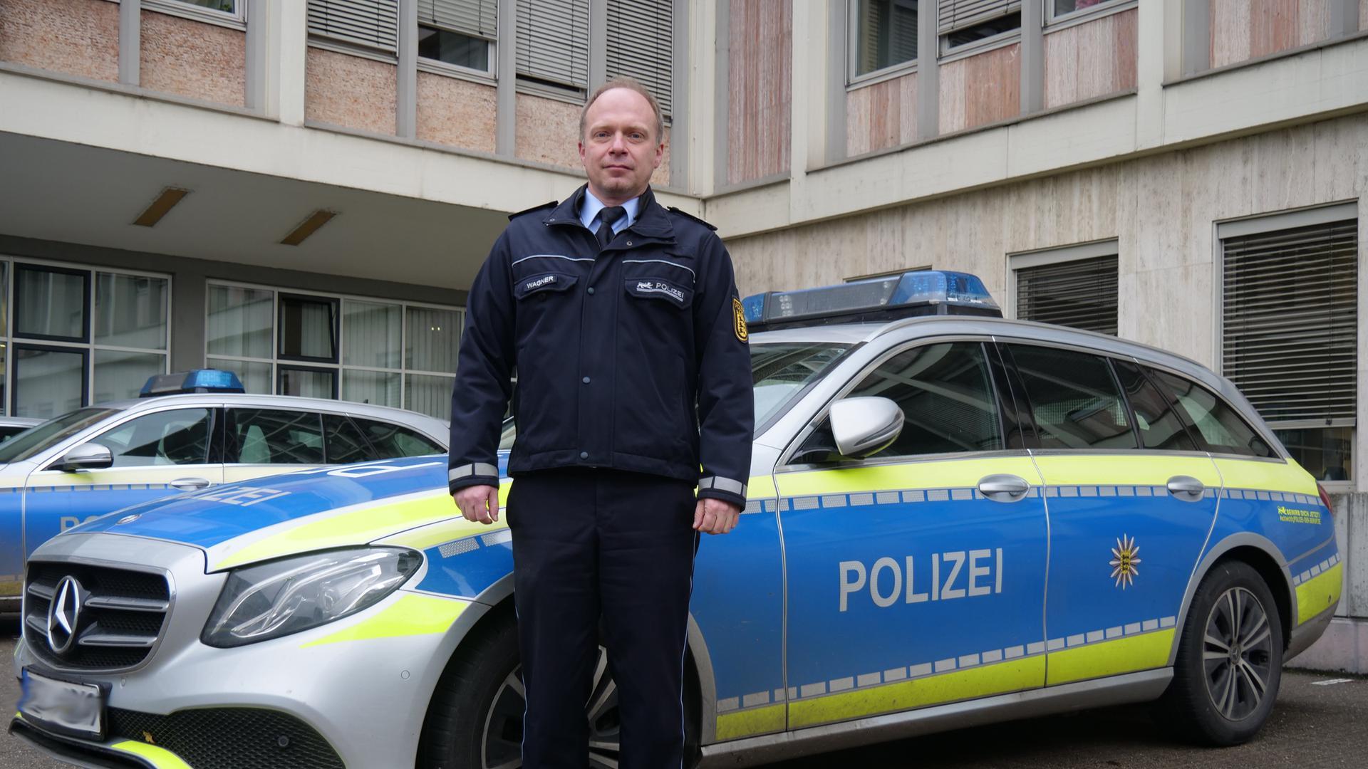 Polizist steht vor einem Einsatzfahrzeug.