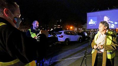 Besim Karadeniz filmt die Grußworte von Frank Neubert (nicht im Bild), von Koki-Interimsgeschäftsführer Sebastian Hilscher und Bürgermeisterin Sibylle Schüssler. Im Hintergrund sind Autos und die Leinwand zu sehen.