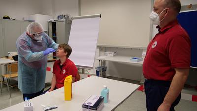 Michael Storz (links), Isabelle Bender und Maik Olpp demonstrieren, wie ein Schnelltest korrekt durchgeführt wird