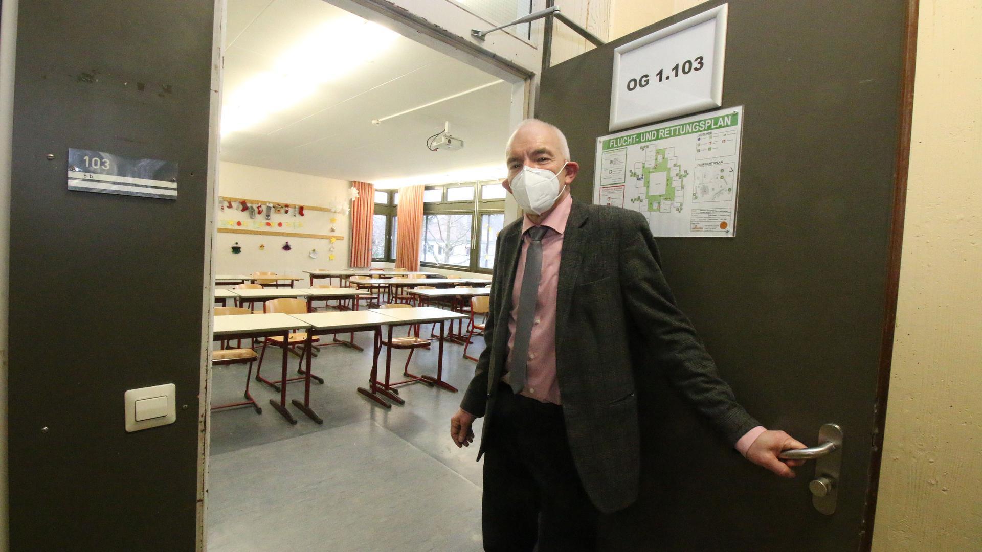 Mann zeigt auf leeres Klassenzimmer