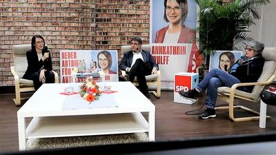 Drei Personen sitzen mit Abstand nebeneinander und halten Mikrofone in den Händen.