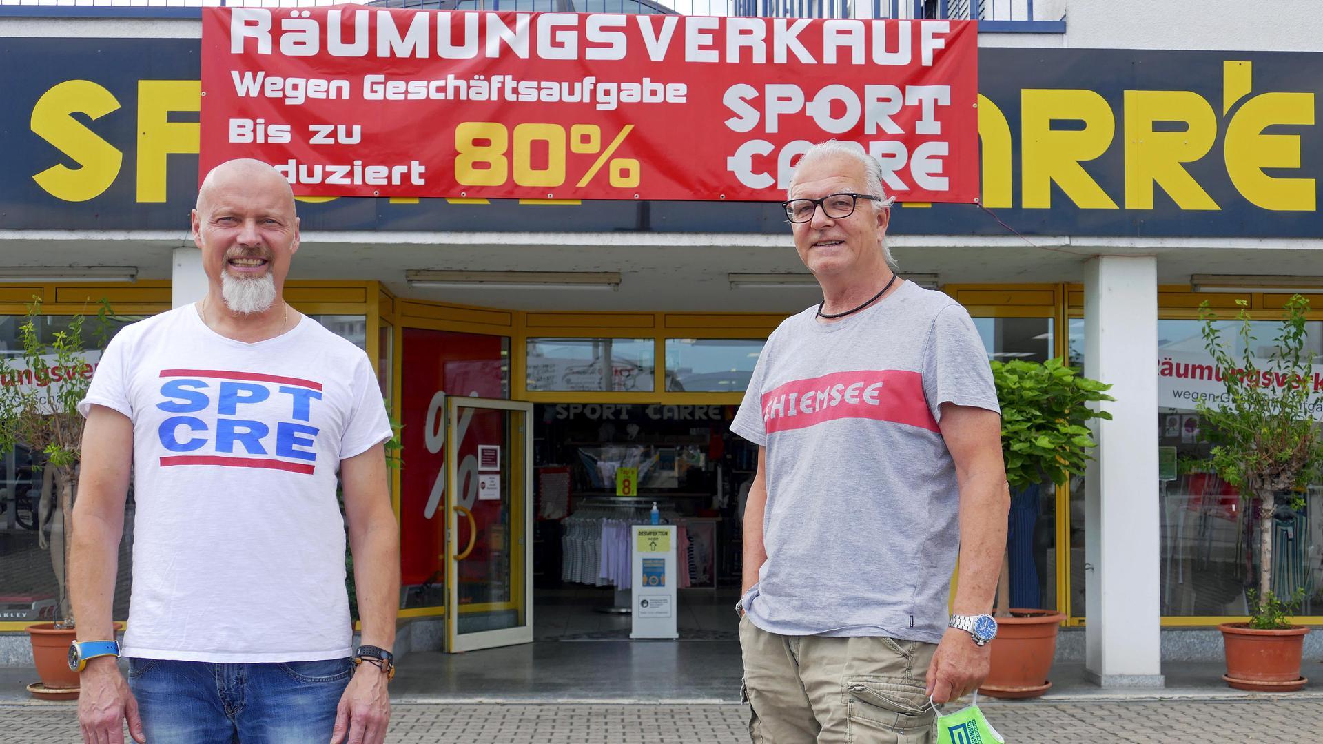 Zwei Männer im T-Shirt stehen vor dem Eingang des Ladengeschäfts.