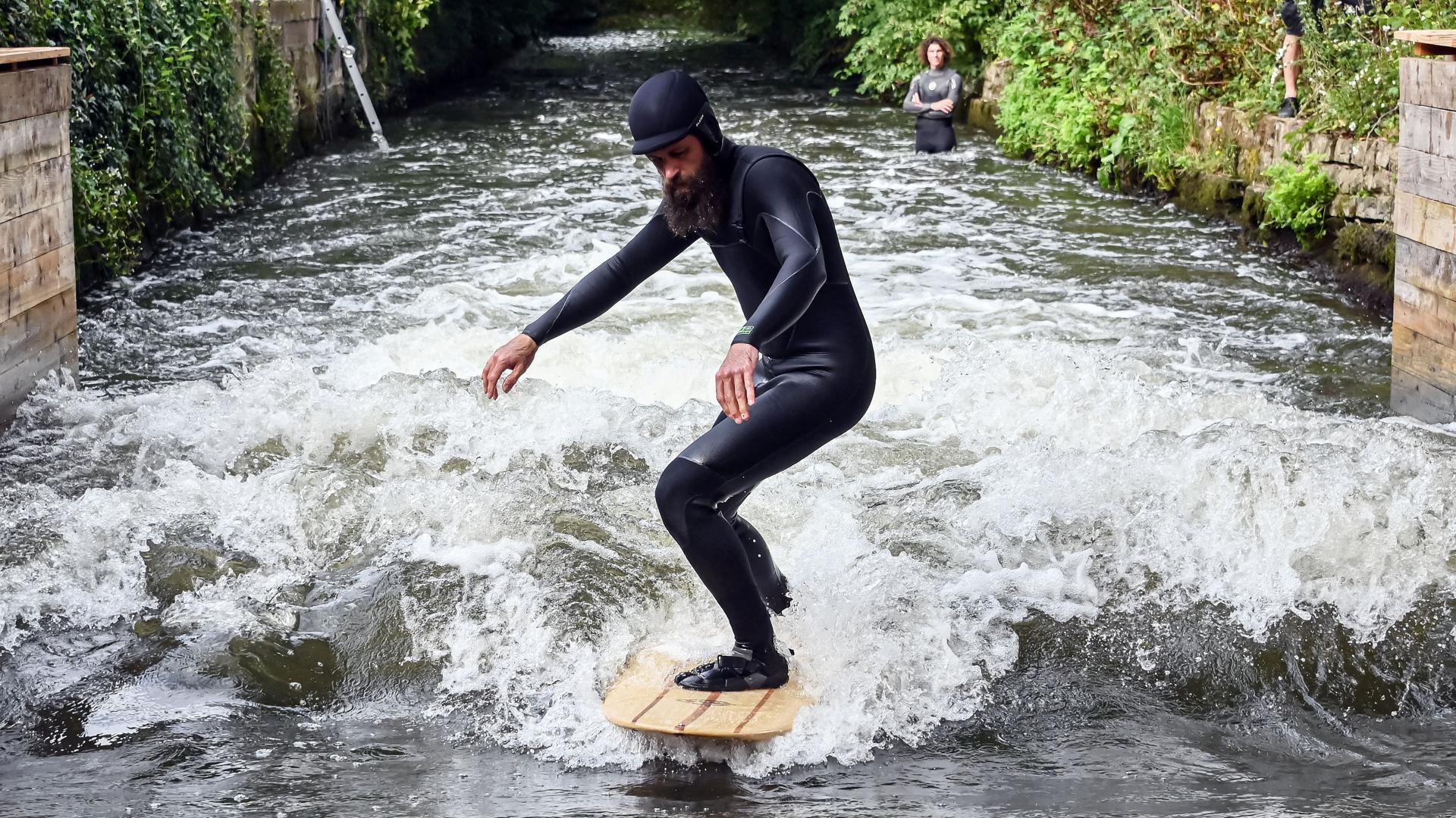 Jonas Buchholz steht auf einem Surfbrett in der Surfanlage Blackforestwave, die am Freitag in Pforzheim offiziell eingeweiht wurde. Die fischdurchlässige Anlage besteht aus einer Stahlrahmenkonstruktion mit absenkbaren Elementen, welche auf einem Hydrauliksystem basiert.