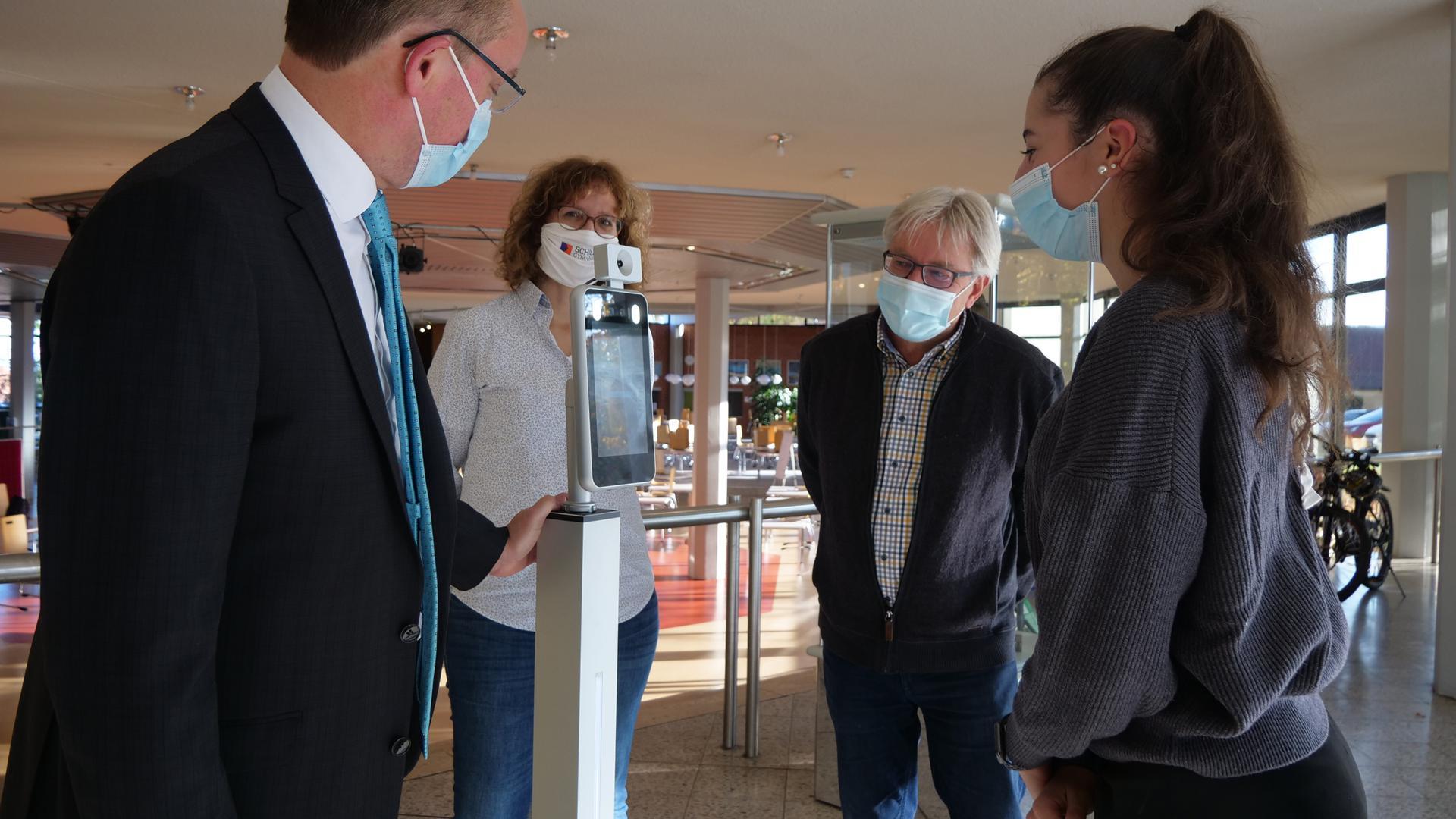 Vier Personen stehen um einen Fieberscanner, eine junge Frau demonstriert den Gebrauch.