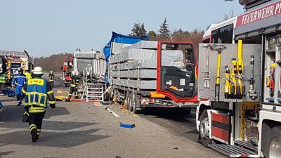 Zwei Lkw, die aufeinander aufgefahren sind, von hinten betrachtet. Feuerwehrleute im Einsatz.