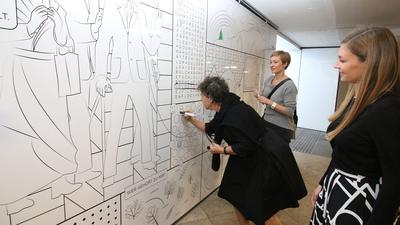 Drei Frauen stehen an einer Wandzeichnung.