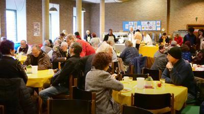 Viele Leute sitzen beim gemeinsamen Essen in der Vesperkirche